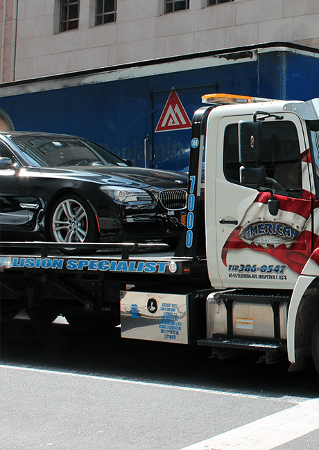 A large towing truck with a black BMW on it's bed parked on the side of the road