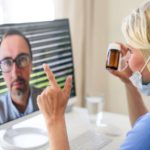 A doctor is discussing a patient's medication over the computer telehealthcare